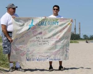 "Clean Power Lake County volunteers hold ""We Are Waukegan"" canvas banner"